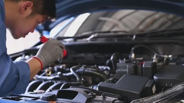 Fiatal ázsiai autószerelő vizsgálja motor motorháztető auto javítási műhely. A szerelő ellenőrzi, hogy van-e ügyfélszolgálat a hosszú út előtt. Üzleti és szállítási koncepció.
