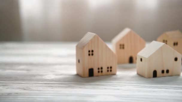 Zavřít malý dřevěný dům a ručně položen velký dům uprostřed vesnice na konci klipu. Realitní dům hypotéku nebo nákupní koncept. Finanční a úvěrové obchody. Dolly střelila do břicha. 4K