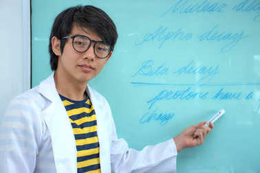 Young chemist posing as a scholar in front of a white board with mathematical formulas