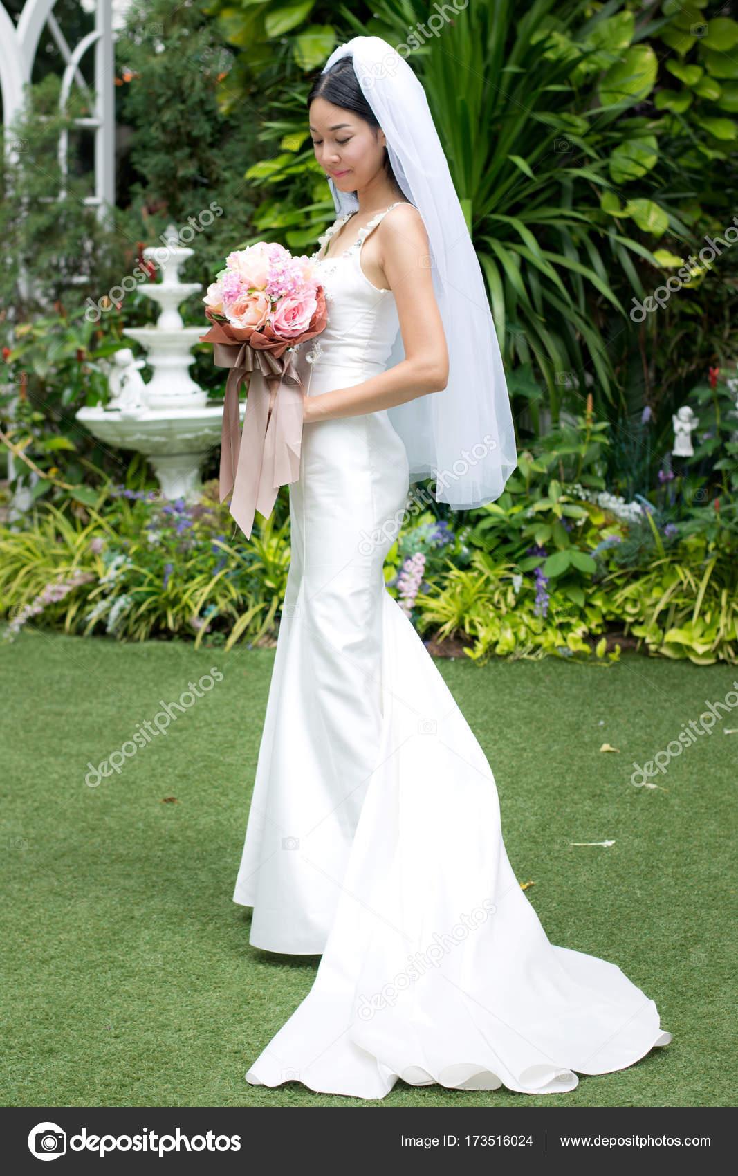 Braut in einem weißen Kleid hält Hochzeit Blumenstrauß mit Bändern ...