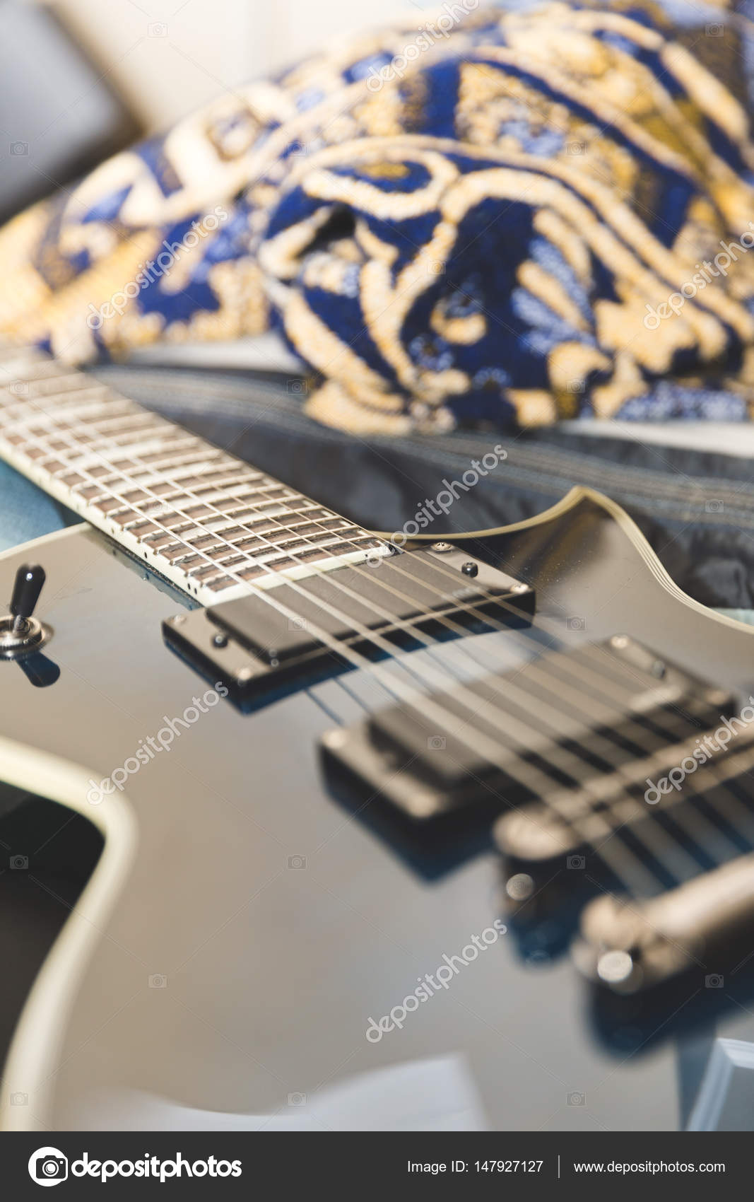 Blue And Black Electric Guitar On A Bed Stock Photo C Theadaptive