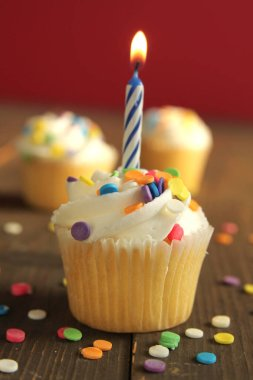 Vanilla birthday cupcake with candle and white icing full of little candies on a orange background