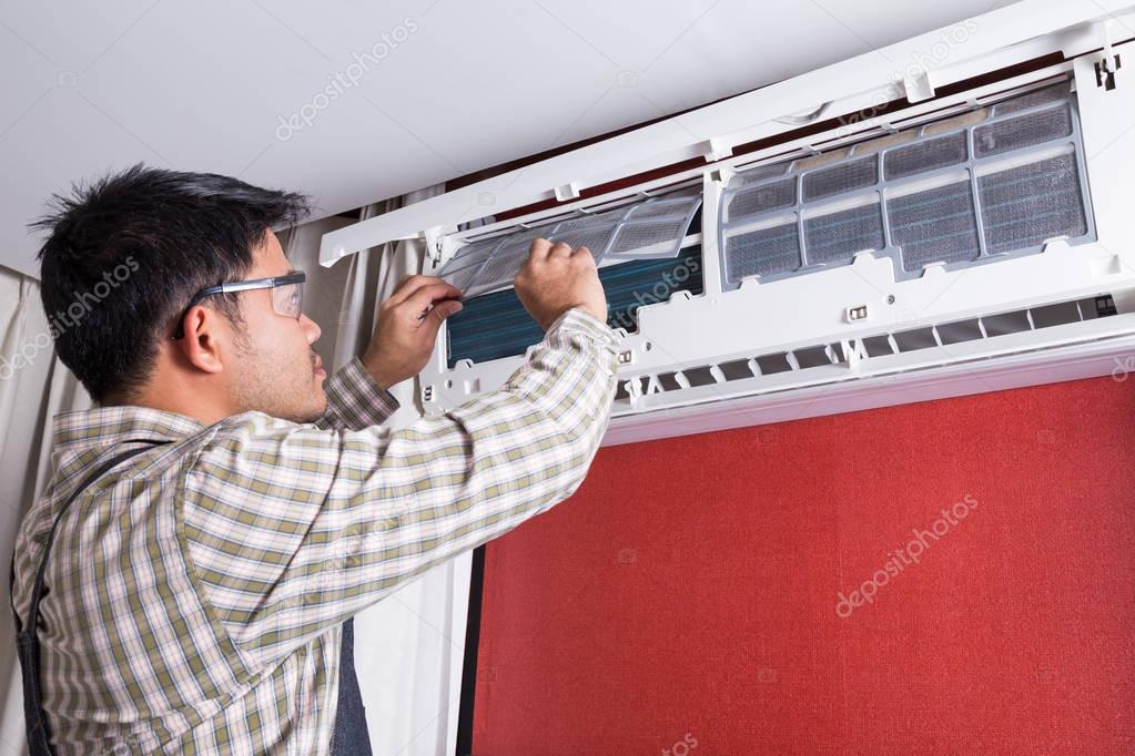 Young man electrician cleaning air conditioning in a client hous