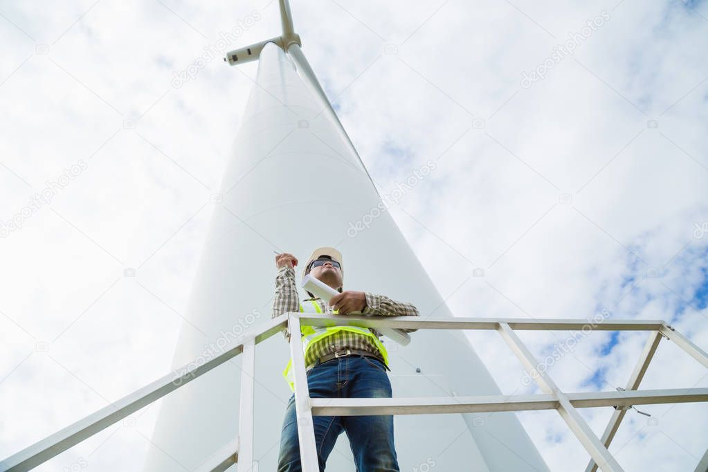 Engineer working at wind turbine site with blueprint
