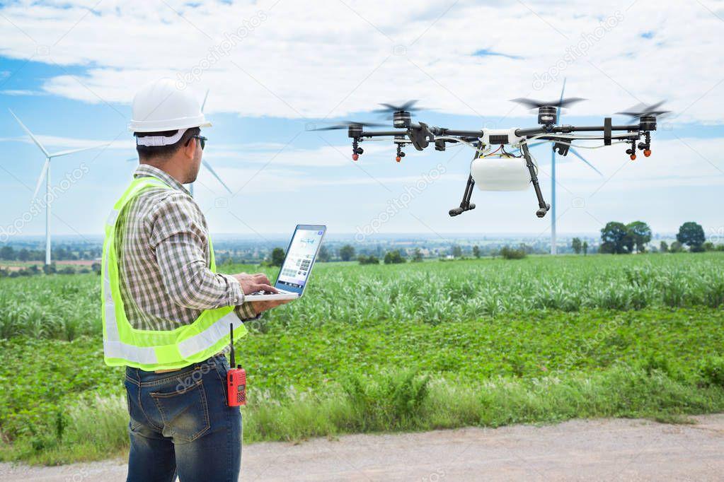 Technician farmer use wifi computer control agriculture drone on sugarcane field