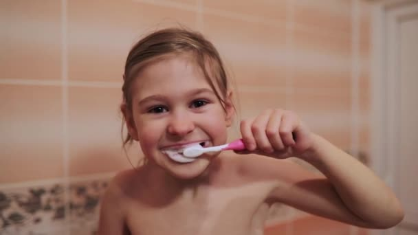 Little kid girl brushes teeth