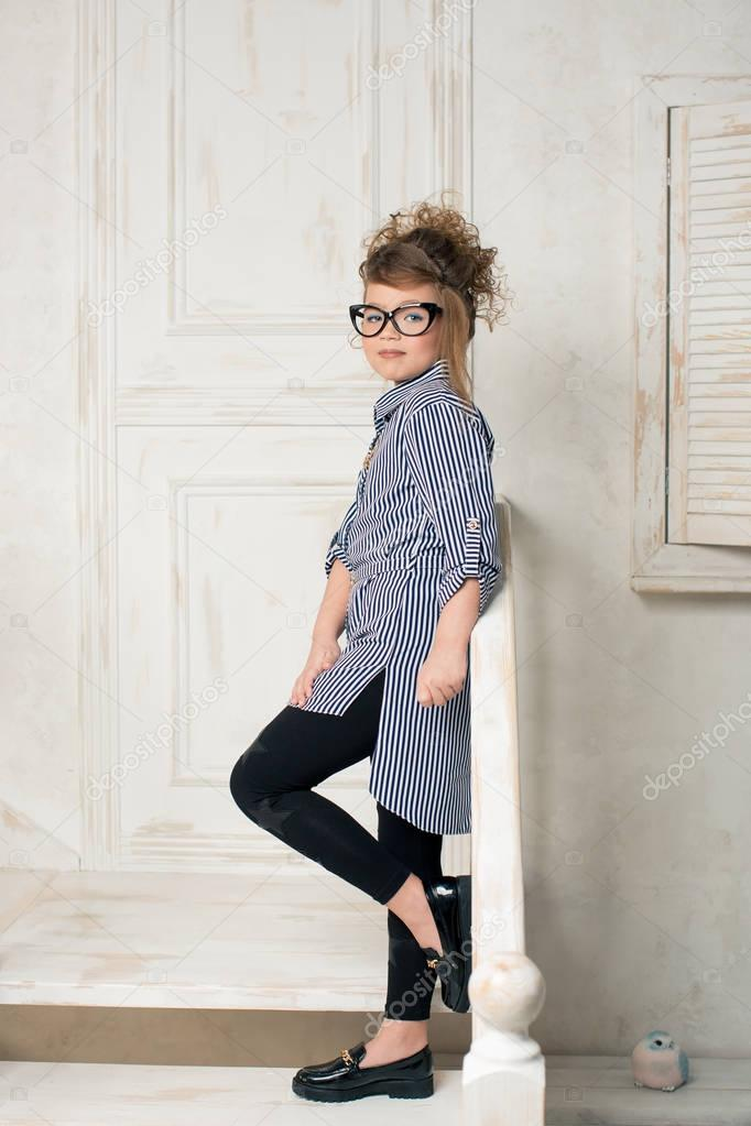 Beautiful young girl in glasses sitting on the stairs of the bright room