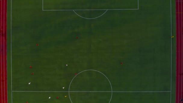 Zelené fotbalové hřiště. Letecký pohled shora. Fotbalisté v herním procesu