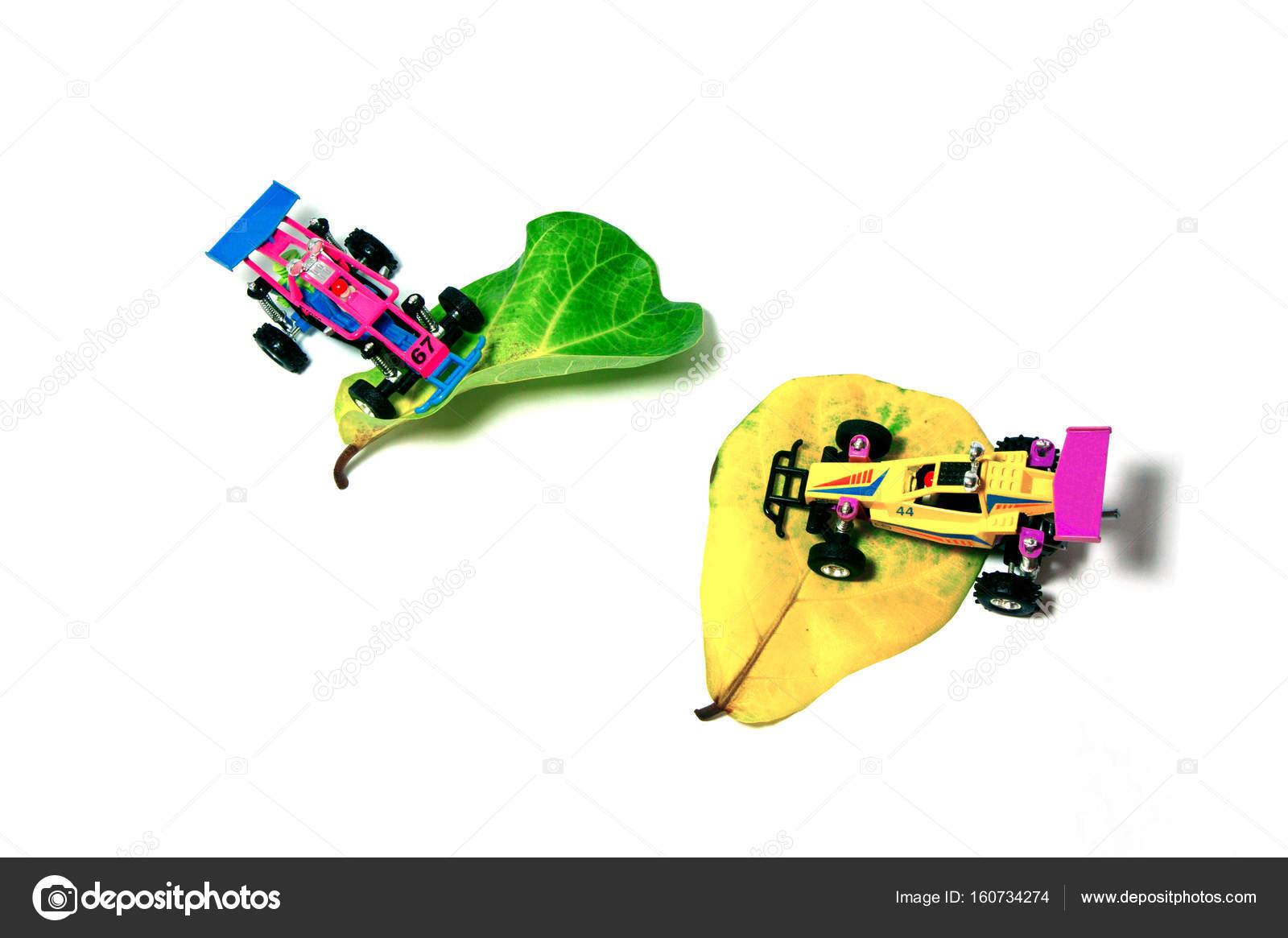 Una macchinina da corsa piccole che riposa sui petali — Foto Stock ...
