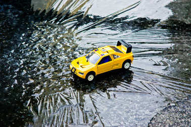 A toy yellow utility vehicle resting on an ice plate.