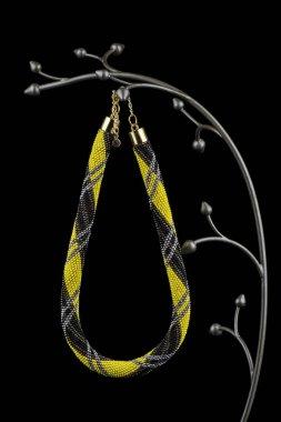 beaded yellow and black necklace hanging on elegant hanger isolated on black background