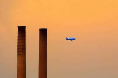 New York, USA - August 09, 2012: blue airship advertising directv in the sunset sky with two smokestacks silhouettes