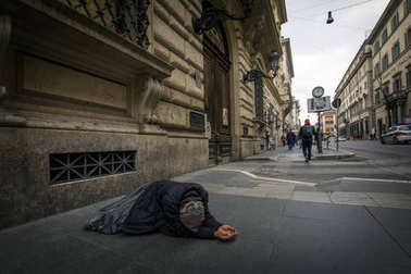 Rome. Italy - 17 November, 2016: A touching scene with beggar woman on a sidewalk in Rome