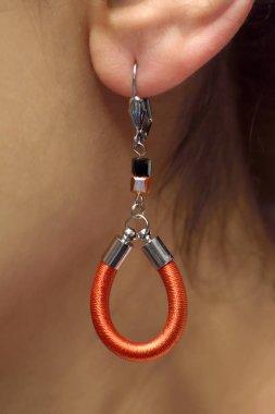Close up earlobe of a woman with beautiful orange earring in it