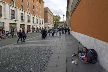 Rome, Italy - November 19, 2016: a touching scene with beggar woman on a sidewalk in Rome