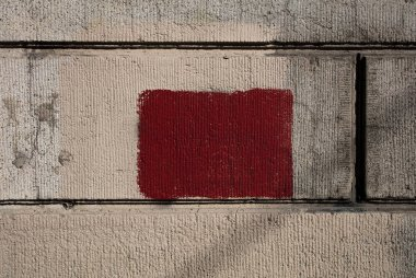 Old shabby gray wall with a red square for text. Texture background.