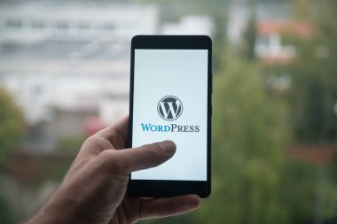 Man holding smartphone with Wordpress logo with the finger on the screen.