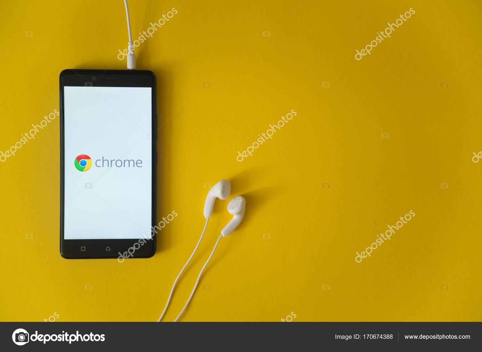 Google chrome logo on smartphone screen on yellow background