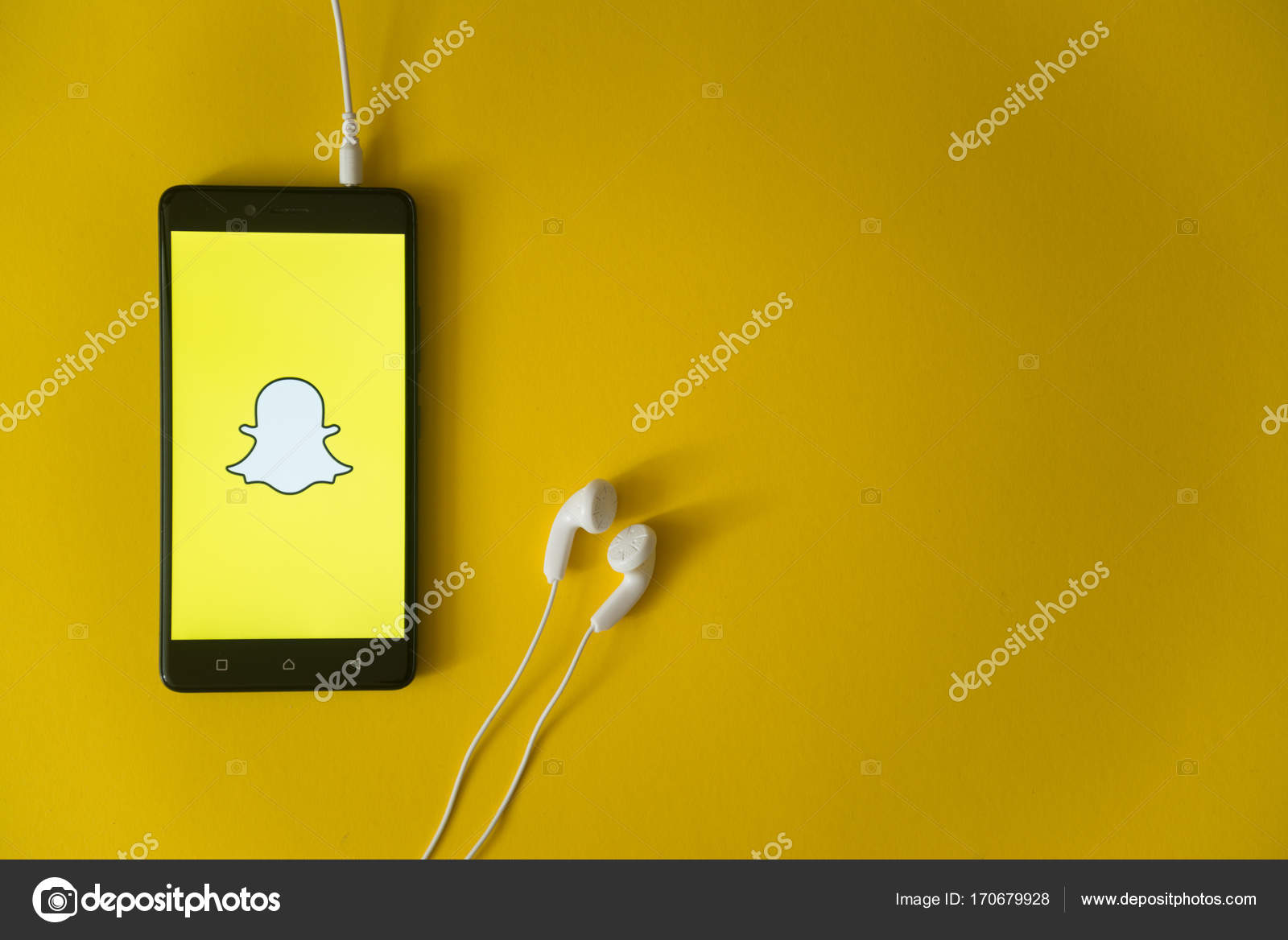 Snapchat logo on smartphone screen on yellow background