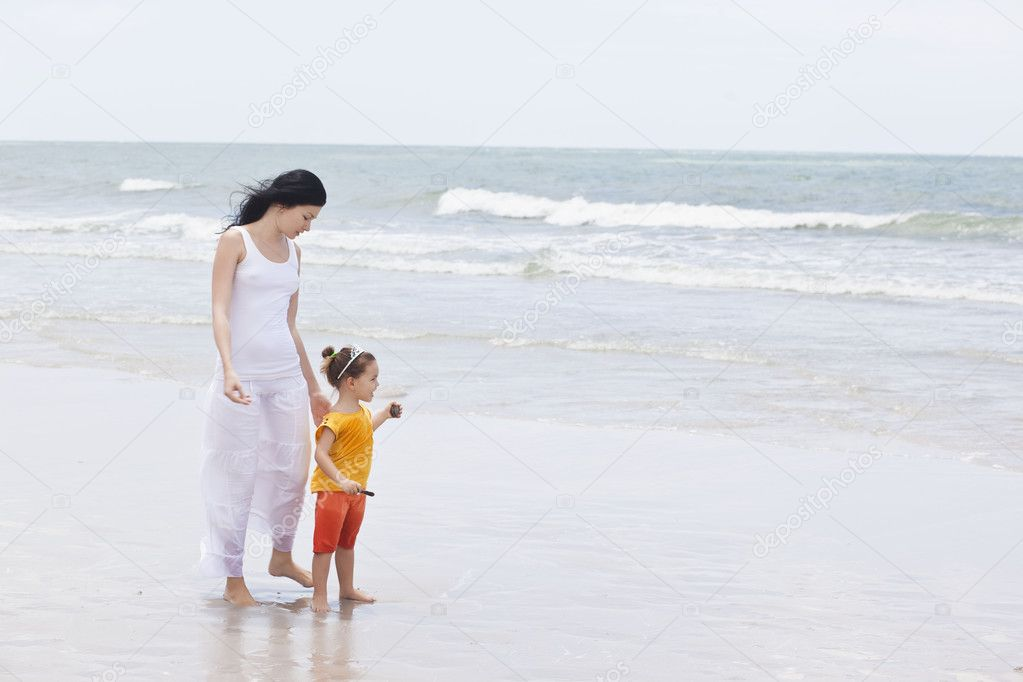 Mother and daughter walking along the beach