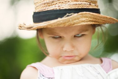 angry child in a straw hat