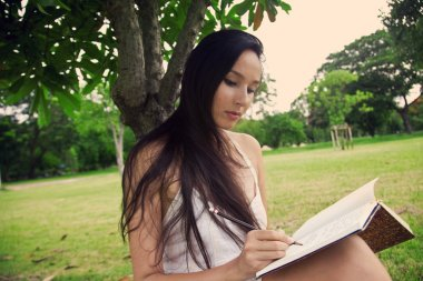 Girl at the park writes in her diary