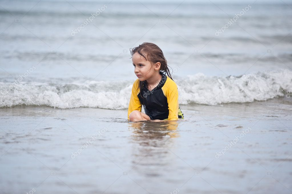 Little girl sitting in waves