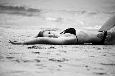 woman lying on sand beach