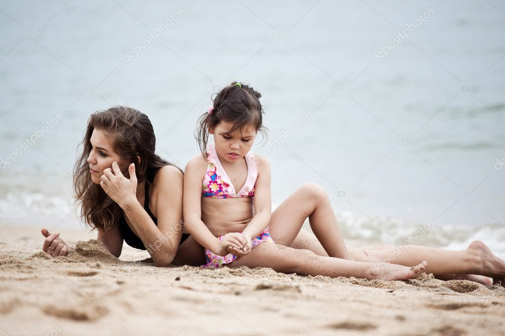 Woman and girl relaxing on the beach