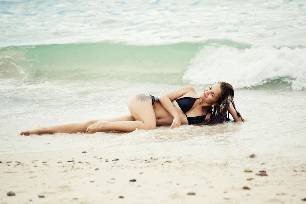woman lying on sand beach
