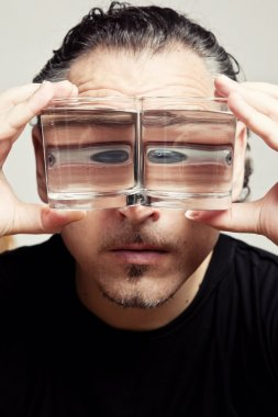 reflection of a male face in glasses with liquid
