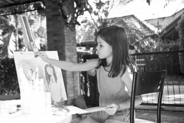 little girl draws a picture