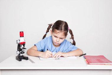 Schoolgirl studying  with microscope