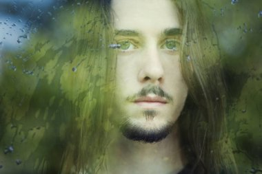 guy with long hair  outside the window