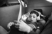 roztomilá holčička v sluchátka poslouchat hudbu v autě
