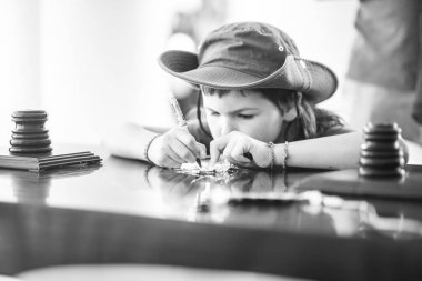 child writing wishes on leaf in White temple in Chiang Rai Thailand, monochrome