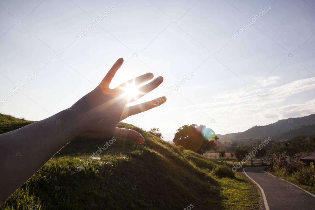 sunset and road through fingers, hand silhouette in sun rays
