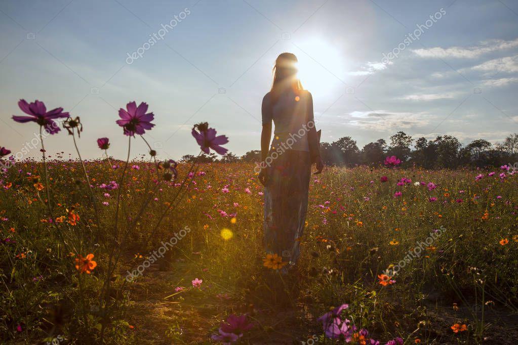 Female silhouette in sunny field of flowers