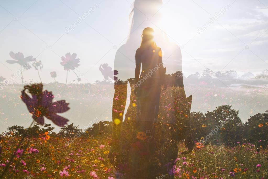 Female silhouette in field of flowers, double exposure