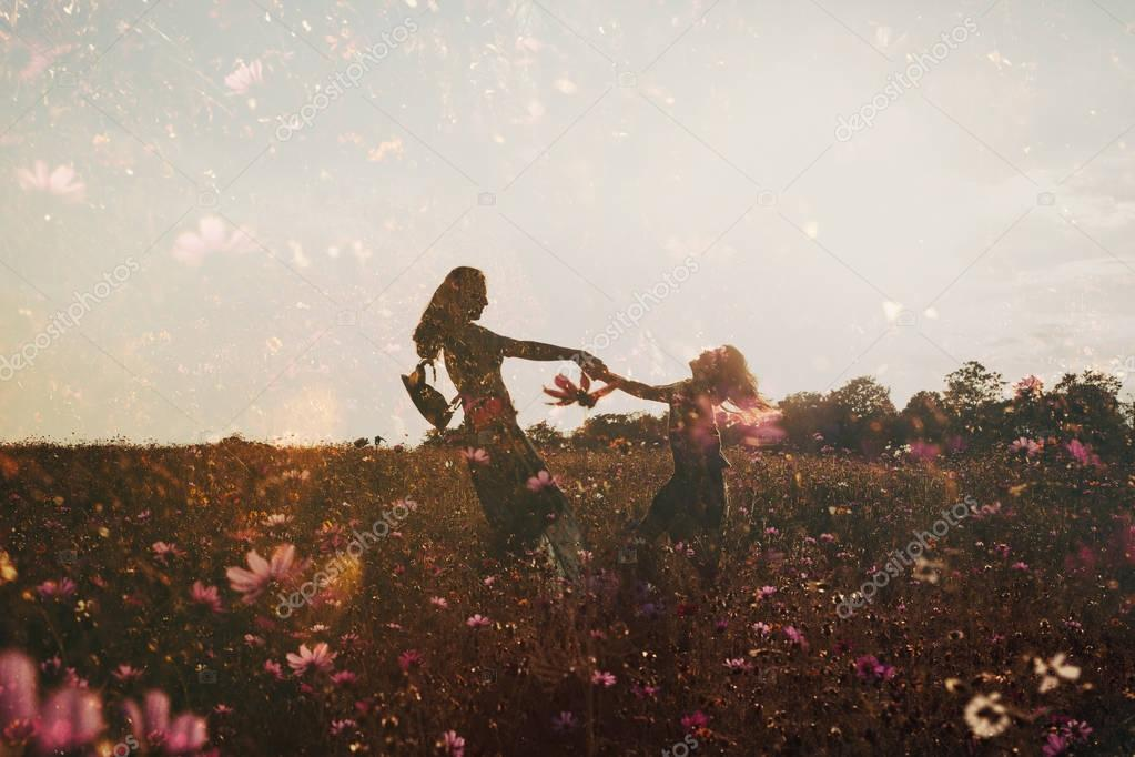 silhouettes of girls having fun holding hands in field of flowers, double exposure