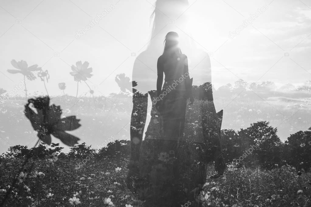 Female silhouette in field of flowers, double exposure, monochrome