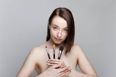 Young beautiful brunette holding in her hand make-up brushes