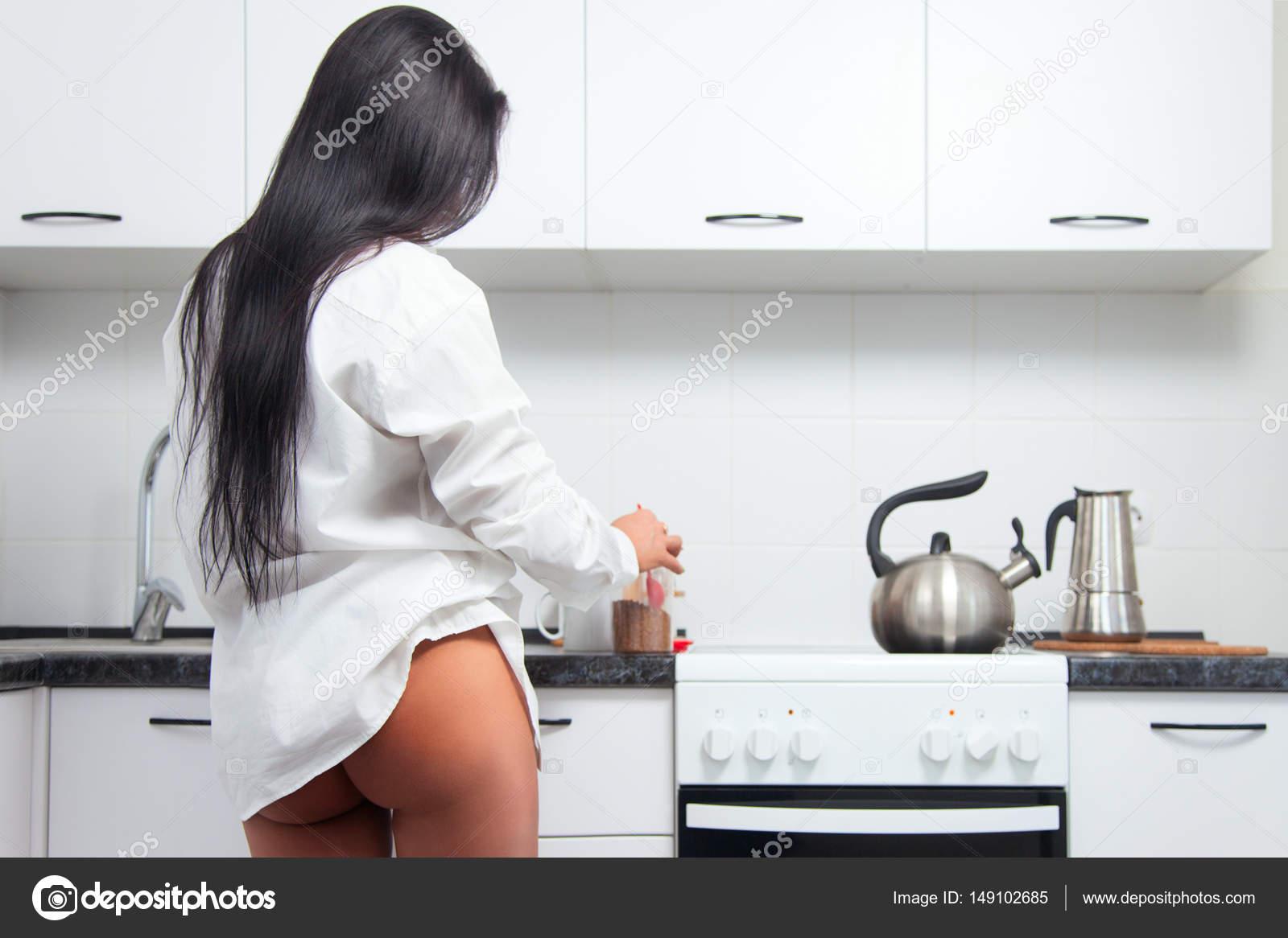 Голая брюнетка на кухне готовит