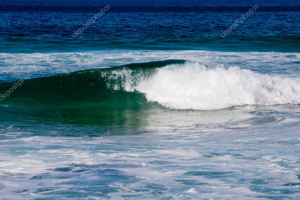 Curling incoming greens and blues in wave - Australia