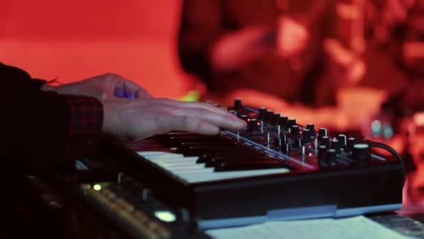 Un musicista suona il sintetizzatore e dietro il batterista segue il ritmo