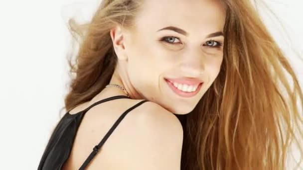 krásné módní holka směje a má ruce na její tvář. má na sobě černé šaty a s radostným výrazem. izolované na bílém pozadí