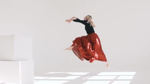 92c311774312 Unga vackra ballerina Dans på vit bakgrund. Röd kjol fladdrande. Projektet  Ballerina– stockfilm