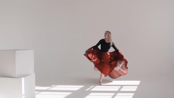 Young beautiful ballerina dancing on white background. Red skirt fluttering. The Ballerina Project.