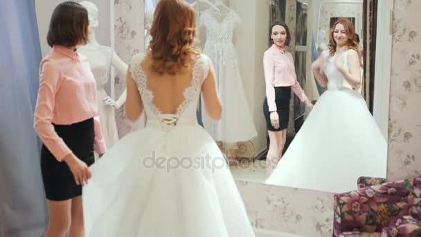 mujer probandose vestido de novia en una tienda con asistente de las