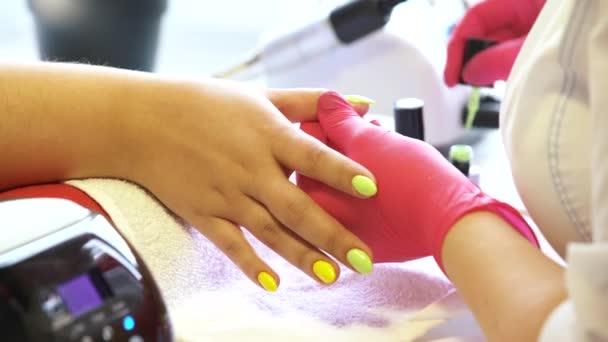 manikůra salonu aplikuje lak na nehty